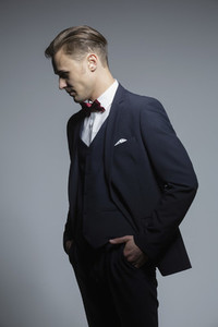 Studio portrait handsome young man in three piece suit