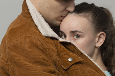 Close up portrait worried young woman in arms of boyfriend