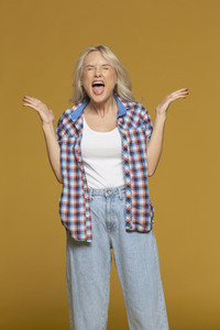 Studio portrait angry woman screaming on yellow background