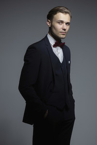 Portrait handsome confident young man in three piece suit