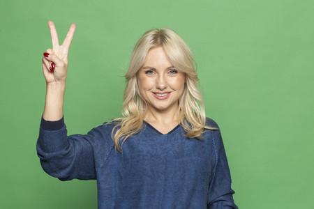 Portrait happy blonde woman gesturing peace sign
