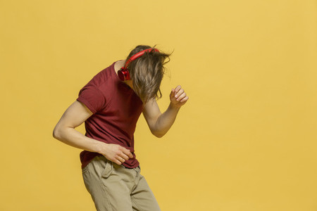 Studio portrait young man with headphones dancing on yellow background