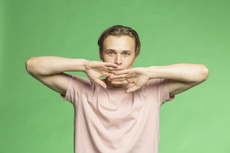 Studio portrait young man with hands covering face