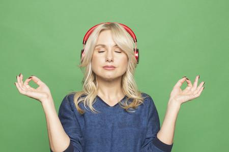 Portrait serene woman meditating with headphones