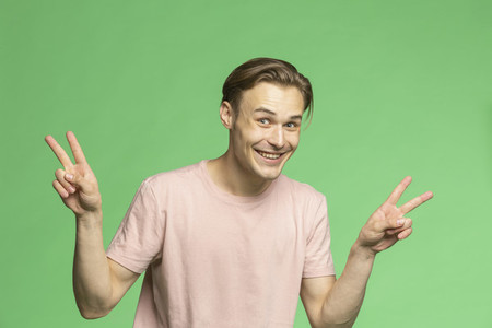 Portrait playful young man gesturing peace sign on green background
