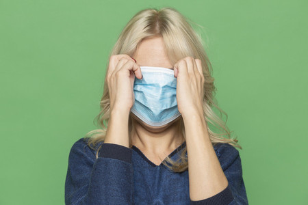 Studio portrait woman covering face with protective face mask