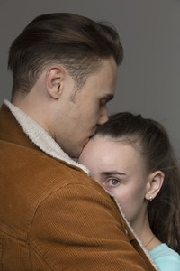 Portrait worried young woman in arms of boyfriend