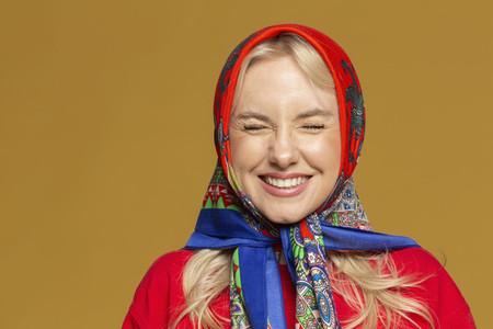 Portrait carefree woman in colorful babushka headscarf