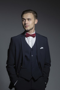 Portrait handsome young man in three piece suit with bow tie