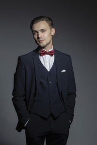 Portrait confident handsome young man in three piece suit