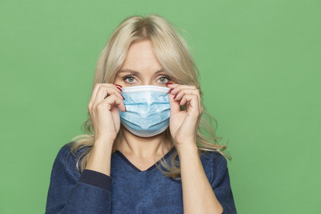 Portrait woman adjusting protective face mask
