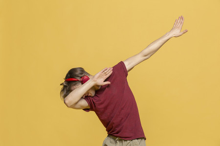 Carefree young man with headphones listening to music and dabbing