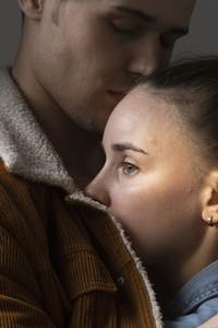 Close up boyfriend hugging worried girlfriend