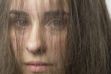 Close up portrait hair in face of beautiful young brunette woman