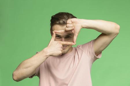 Studio portrait young man gesturing finger frame on green background