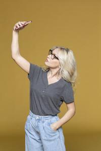 Studio portrait woman taking selfie on yellow background