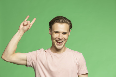 Portrait carefree young man gesturing horn sign