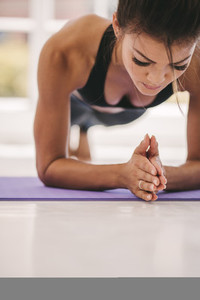 Woman holding plank pose in fitness studio