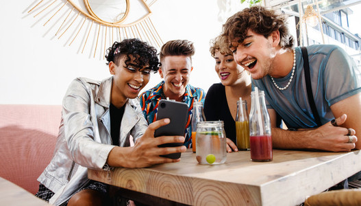 Young people video calling their friends in a restaurant