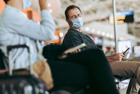 Male traveler sitting at airport terminal in pandemic