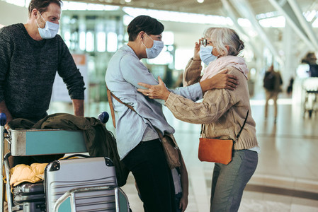 Senior woman receiving her family at airport after pandemic