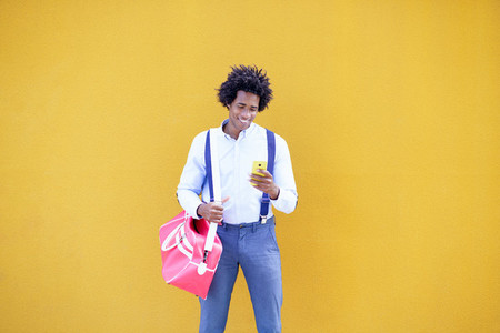 Black man with afro hairstyle carrying a sports bag and smartphone in yellow background