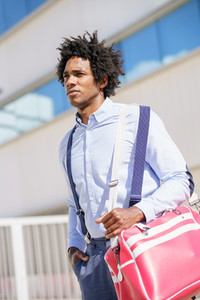 Black worker walking near an office building with a sports bag