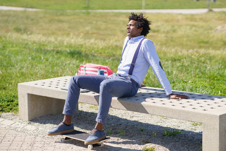 Black man with afro hair taking a coffee break sitting on a park bench