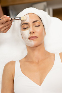 Aesthetics applying a mask to the face of a Middle aged woman in modern wellness center