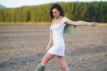 Asian woman  walking in the countryside  wearing a white dress and green wellies