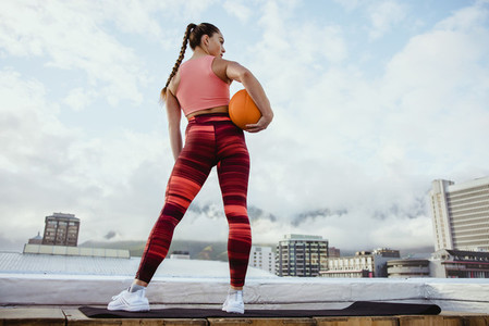 Athlete woman with basketball on rooftop