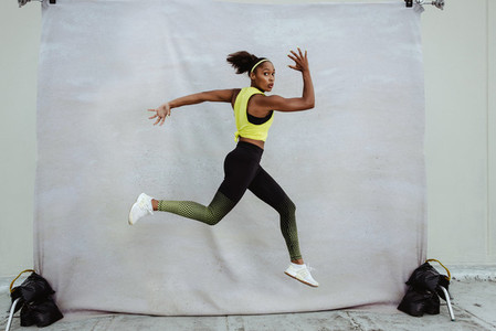 Athlete woman exercising on a building terrace
