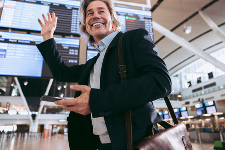 Businessman waving in airport