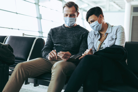Couple using phone while waiting for their flight