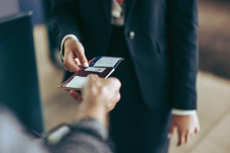 Airport staff checking passport of passenger
