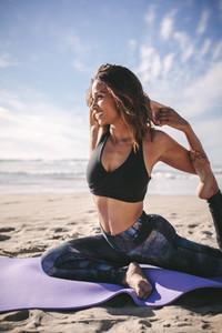 Happy woman doing yoga exercise on beach