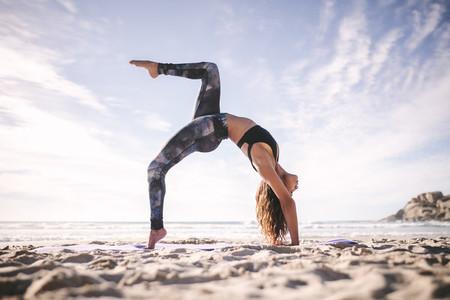 Fit woman practicing one legged upward bow yoga pose