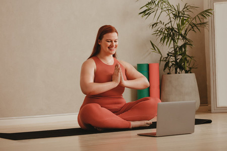 Woman doing yoga meditation watching online fitness session