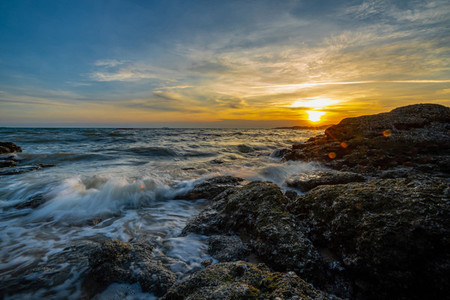 Sea waves crashed against rocks in the sunset at Pattaya Thailan