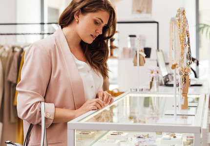 Female buyer looking at display case in a boutique  Woman in boutique choosing accessories