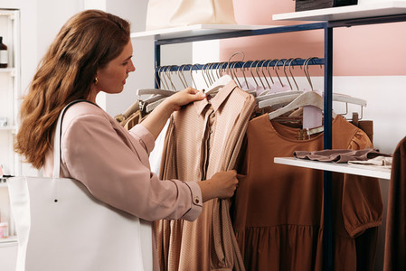 Woman standing at a rack holding hanger with dress in a small boutique