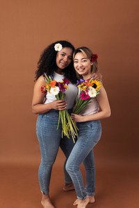 Asian and mixed race women posing against a brown background  Two smiling females with bouquets looking at camera