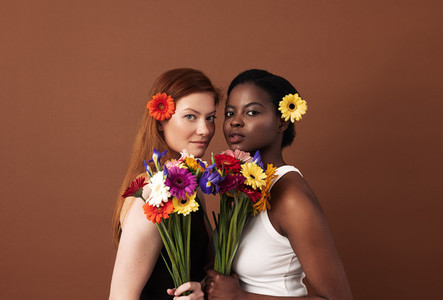 Two women of different races with flowers in their hairs holding bouquets  Caucasian and African American females looking at camera in a studio