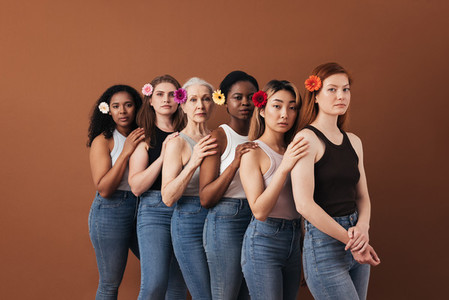 Six diverse female standing together over brown background  Women of different ages with flowers in their hair