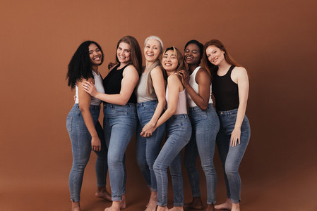 Six women of different ages and body types smiling and laughing over brown background