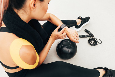High angle of female athlete checking pulse on smart watch after exercises indoors