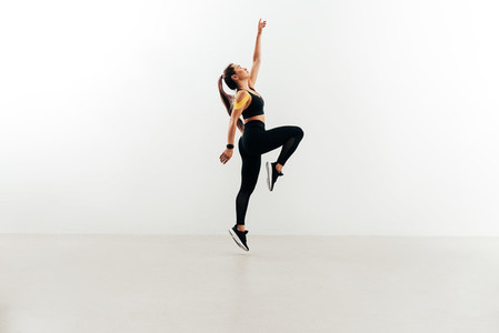 Woman jumping in the air against white wall raising one hand up  Young female in sports clothes warming up