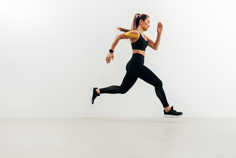 Side view of woman running against a white wall  Jogger with kinesiology tape on her shoulder sprinting