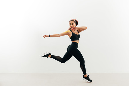 Asian woman look back while jumping and running against a white wall