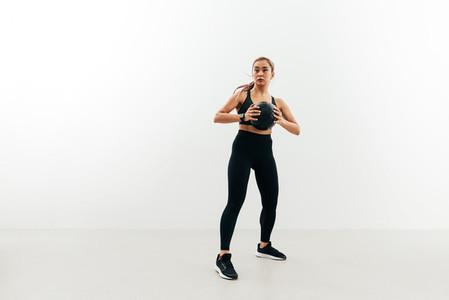 Full length of young sportswoman holding medicine ball against a white wall looking away